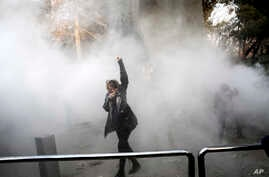 A university student attends a protest inside Tehran University while a smoke grenade is thrown by anti-riot Iranian police, in Tehran, Iran, Dec. 30, 2017. A wave of spontaneous protests over Iran's weak economy swept into Tehran  Saturday, with col
