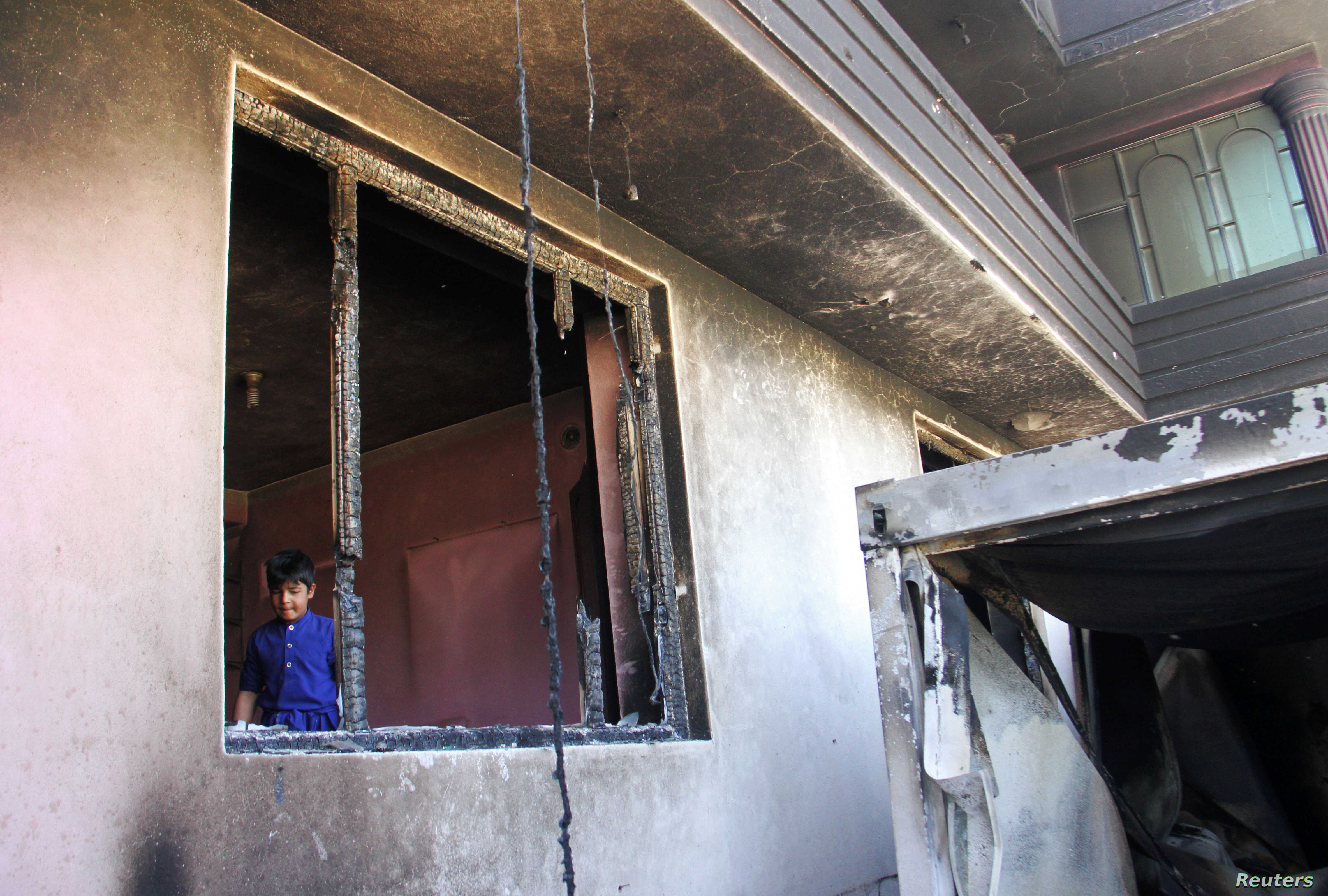 An Afghan boy is seen inside a burnt building after a Taliban attack in Ghazni city, Afghanistan, Aug. 15, 2018.