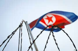 A North Korean flag is seen behind razor wire on top of a wall at the North Korean embassy in Kuala Lumpur, Malaysia, March 9, 2017