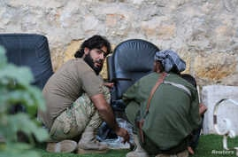 Rebel fighters of al-Jabha al-Shamiya (Levant Front) have their meal in the rebel-held al-Sheikh Said neighbourhood of Aleppo, Syria Sept.1, 2016.