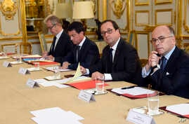 French President Francois Hollande, flanked by his Interior Minister Bernard Cazeneuve, right, and Prime Minister Manuel Valls, 2nd left, looks on during a meeting with French representatives of the different religion at the Elysee Palace in Paris, W