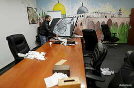 A man carries a photo inside the offices of the The Islamic Movement northern branch in Israel after Israel outlawed the Movement today, in Umm al-Faham, northern Israel, Nov. 17, 2015.
