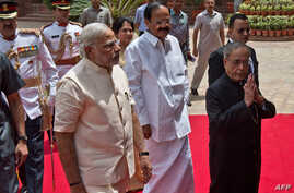 Indian President Pranab Mukherjee (R) arrives with Indian Prime Minster Narendra Modi (L) to address the joint session of Parliament in New Delhi, India, June 9, 2014.