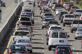 FILE - A motorcyclist rides between lanes as traffic backs up on U.S. Highway 101 in Mill Valley, Calif., May 26, 2011. California, 16 other states and the District of Columbia sued the Trump administration on May 1, 2018, over its plans to scrap sta...