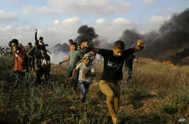 Palestinian protesters take cover from tear gas fired by Israeli troops as others burn tires near the Gaza Strip's border with Israel, during a protest east of Khan Younis, in the Gaza Strip, June 1, 2018.