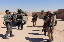 FILE - Afghan Special Forces and policemen prepare for battle with the Taliban on the outskirts of Lashkar Gah, capital of Helmand, Afghanistan, Oct. 10, 2016.