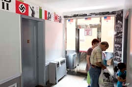 FILE - Residents of an apartment building pass posters of Adolf Hitler and Benito Mussolini in the hallway as they enter an apartment, Aug. 23, 2017, in the Queens borough of New York.