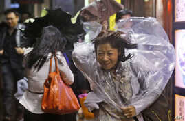 A woman braves strong wind in Hong Kong Monday, Sept. 15, 2014.