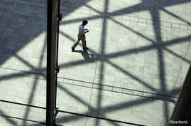 FILE - A man walks under the shadow of sunshade at a building in Tokyo. Would a man-made chemical sunshade — perhaps formed by clouds of reflective sulfur particles sprayed high in the Earth's atmosphere — be less risky than a harmful rise in global
