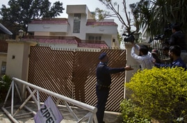 Pakistani police officers stop cameramen filming a house, where family members of slain Al-Qaida leader Osama bin Laden are believed to be held, Saturday, March 17, 2012 in Islamabad, Pakistan. A Pakistani official says a judge has allowed authoritie