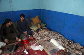 Nawid, a 21-year-old student who lost his brother and who was himself wounded in a deadly Taliban suicide attack earlier this month, receives visitors as he lies in bed at home in Kabul, Afghanistan, Jan. 29, 2019.