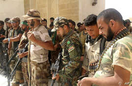Newly arrived Iraqi Shiite militiamen check their weapons in the predominately Sunni city of Nukhayb, in southwest Iraq, May 21, 2015. Many analysts fear deep sectarian divisions will cripple the fight against the Islamic State group.