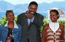 """FILE - Idrissa Ouedraogo of Burkina Faso seen between actresses Netsayi Chigwendere (L) and Nthati Moshesh (R) during a photo call for their film """"Kini and Adams"""", May 10, 1997."""