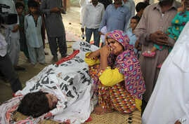 """FILE - In this picture taken on July 18, 2016, the mother of Pakistani slain social media star Qandeel Baloch mourns besides her dead body in Shah Sadderuddin, Pakistan. Baloch was killed by her brother for what he called """"intolerable"""" behavior."""