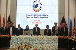 Afghan President Ashraf Ghani, center, and delegates stand for the national anthem during the second Kabul Process conference at the Presidential Palace in Kabul, Feb. 28, 2018.