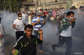 Anti-government and supporters of ousted Egyptian President Mohamed Morsi run after riot police released tear gas along a road at Kornish El Nile, which leads to Tahrir Square, Cairo, October 6, 2013.