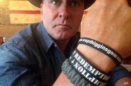 "FILE - In this June 2, 2016, photo, Clay Higgins, then a candidate for Congress, poses for a photograph in Lafayette, La. His wristband is printed with the word ""redemption."" The Republican dubbed the ""Cajun John Wayne"" set his sights on and won a co"