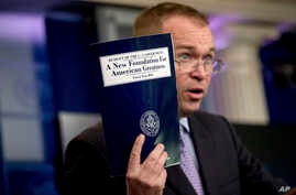 FILE - Budget Director Mick Mulvaney holds up a copy of President Donald Trump's proposed fiscal 2018 federal budget as he speaks to members of the media in the Press Briefing Room of the White House in Washington, May 23, 2019.