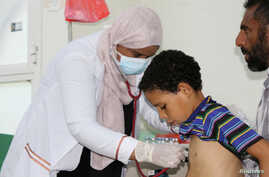 FILE - Nahla Arishi, a pediatrician, checks a boy infected with diphtheria at the al-Sadaqa teaching hospital in the southern port city of Aden, Yemen, Dec. 18, 2017.