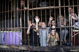 Inmates gesture from behind bars in Aleppo's main prison May 22, 2014. Syrian troops have broken a year-long rebel siege on Aleppo's main prison after heavy fighting with al Qaeda fighters and other Islamist brigades, the Syrian Observatory for Human