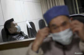 A patient (L) with fever receives treatment at the hospital where a 67-year-old H7N9 patient is being treated, in Hangzhou, Zhejiang province, April 3, 2013.