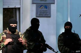 Armed men stand guard in front of the entrance of the Mejlis of the Crimean Tatar people, the single highest executive-representative body of the Crimean Tatars, in Simferopol on Sept. 16, 2014.