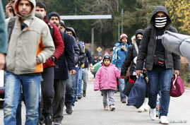 Migrants walk along a street after passing the Austrian-German border near Wegscheid, Germany, Nov. 12, 2015.