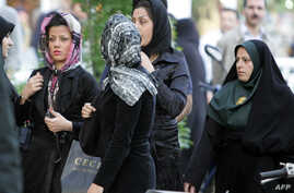 An Iranian policewoman (R) warns women about their clothing and hair during a crackdown to enforce Islamic dress code in Tehran, April 23, 2007. AFP/Atta Kenare