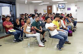 Mexican nationals wait to be seen at the Consulate General of Mexico, March 3, 2017, in Miami.
