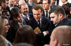 French President Emmanuel Macron, center, speaks with guests next to Minister of the Ecological and Social Transition Nicolas Hulot, left, and French President of the Young Farmers Association Jeremy Decerle, right, after he delivered a speech to th