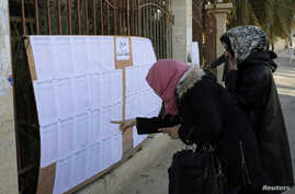 People look for their names at a polling station, Benghazi, Feb. 20, 2014.