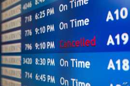 A departure board at the Philadelphia International Airport shows that US Airways Flight 796 to Tel Aviv has been canceled, July 22, 2014.