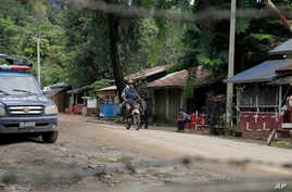 Local residents ride a motorcycle past a police checkpoint in Myanmar's border town of Maungdaw, Rakhine State, Oct. 13, 2016.