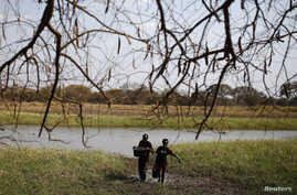 FILE - Rebel fighters collect water to drink from a swamp in a rebel camp in Jonglei State.