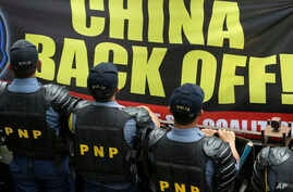 Riot police stand guard as protesters hold up a large anti-China banner outside the Chinese Consulate at the financial district of Makati city, east of Manila, Philippines, July 24, 2013.