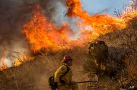 Firefighters battle a wildfire on Cajon Boulevard in Keenbrook, Calif., on Aug. 17, 2016.