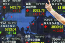 A man gestures in front of a securities firm's electronic stock board in Tokyo, Aug. 16, 2012.