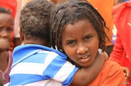 A child holds another refugee in Kenya's Dadaab refugee camp, September 20, 2016.