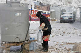 A Syrian refugee carries bread and bottles of water during a winter storm in Zahle town, in the Bekaa Valley, Dec. 11, 2013.