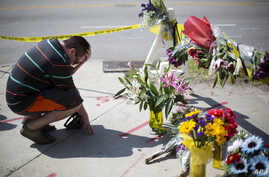 Noah Nicolaisen, of Charleston, S.C., kneels at a makeshift memorial, Thursday, June 18, 2015, down the street from where a man opened fire Wednesday night during a prayer meeting inside the Emanuel AME Church, killing several people in what authorit...