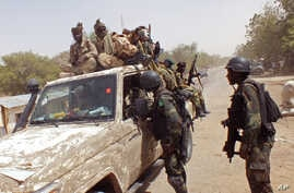 FILE - In this photo taken on Thursday, Feb. 19, 2015, Chadian soldiers on top of a truck, left,  speak to Cameroon soldiers, right, standing next to the truck, on the border between Cameroon and Nigeria as they form part of the force to combat regio