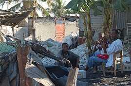 A family in the destroyed town of Carrefour, Haiti sits amid the charred rubble of their home, 25 Jan 2010