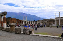 FILE - Tourists stroll past the remains of Pompeii's forum.