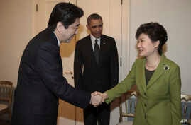 South Korean President Park Geun-hye, right, shakes hands with Japanese Prime Minister Shinzo Abe, left, as U.S. President Barack Obama looks on before their trilateral meeting at the U.S. Ambassador's Residence in the Hague, Netherlands, Tuesday, Ma