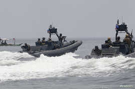 """FILE - U.S. and Philippine Navy servicemen aboard patrol boats conduct a boat manoeuvre exercise past a fishing boat during a joint annual military exercise called """"Carat"""" at the former U.S. military base Sangley Point in Cavite city, west of Manila,"""