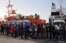 Migrants line up as they are helped by members of Spanish Red Cross after arriving on a rescue boat at the port of Algeciras, southern Spain, July 22, 2018.