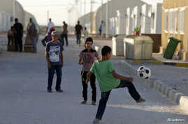 Syrian refugee children play with a soccer ball at the Mrajeeb Al Fhood refugee camp, July 1, 2014.