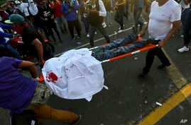 A demonstrator, who was shot in the head and apparently died, is carried by paramedics after clashes erupted during a march against Nicaragua's President Daniel Ortega in Managua, Nicaragua, May 30, 2018.