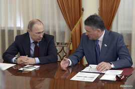 Russian President Vladimir Putin (L) talks to Federation Council Deputy Chairman Yuri Vorobyov during a meeting with members of the Federation Council at the Novo-Ogaryovo state residence outside Moscow, March 27, 2014.