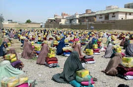 Afghan burqa clad women sit after they received ration aid in Kandahar, Afghanistan, 04 May 2016.